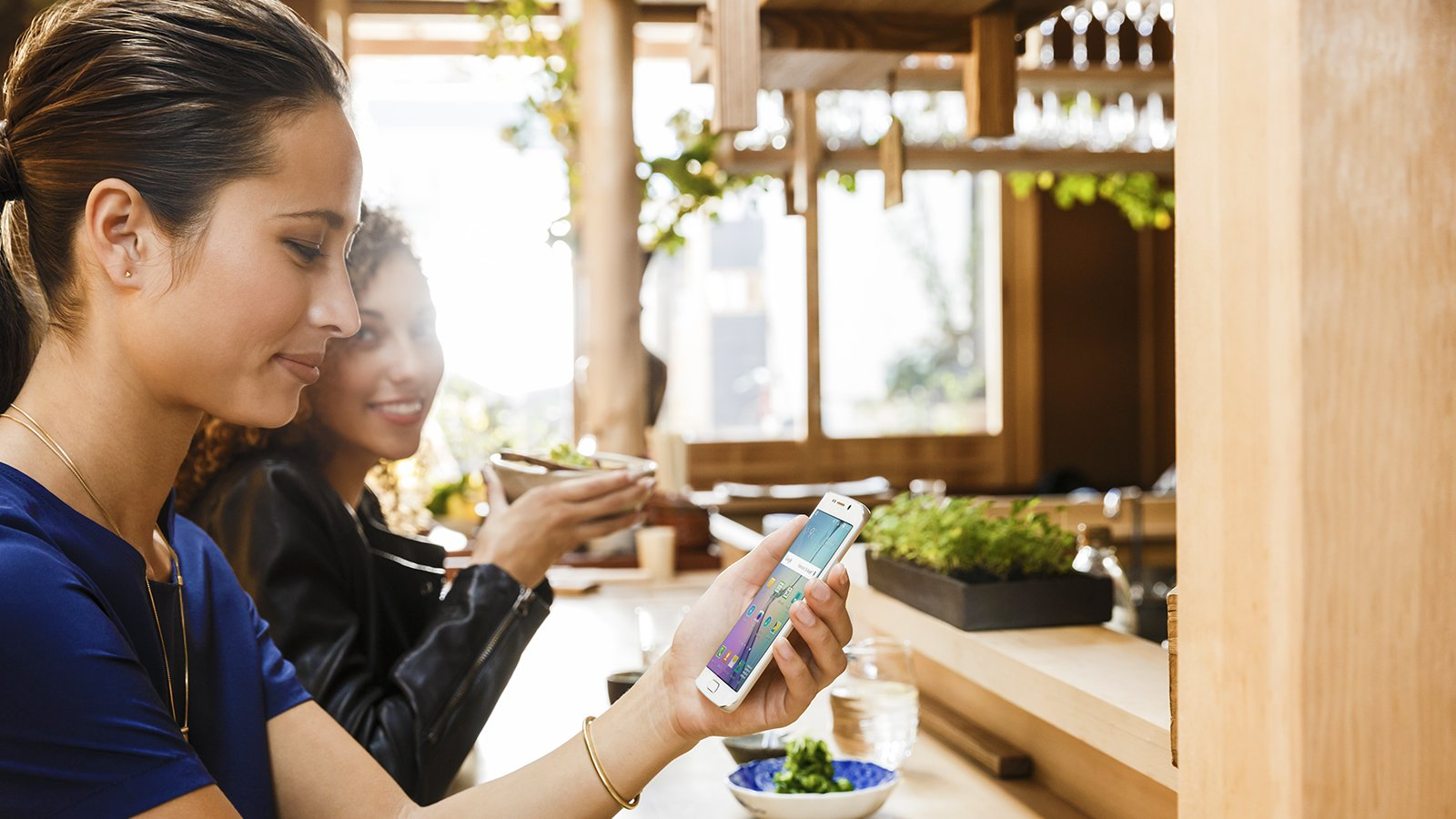 Woman holding smart phone chatting with another woman at bar.