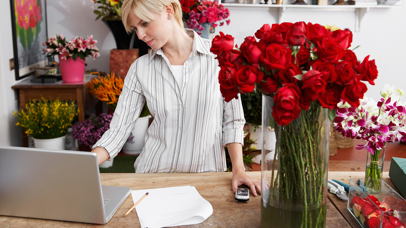 A woman standing at a table inside a flower shop, looking at her laptop.