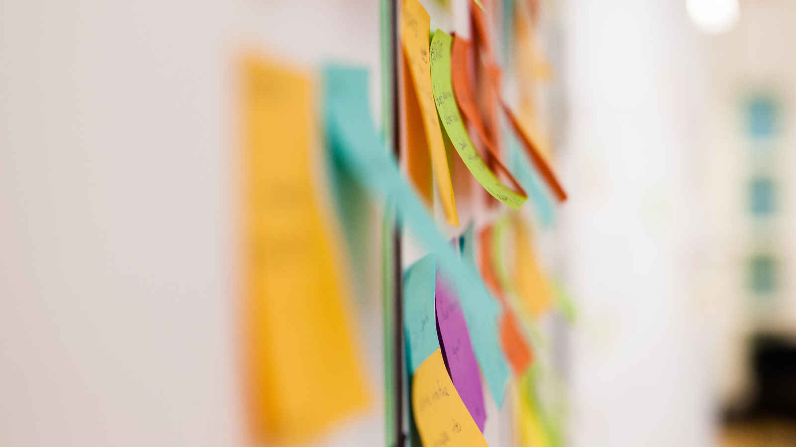 Close up of green and orange post-it notes.